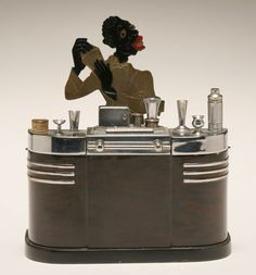 Ronson black bartender 'Touch Tip' cigarette lighter with humidor compartments. A Black Americana figure stands behind a ca. streamline Art Deco bar with miniature size barware affixed to top. Streamline Art, Streamline Moderne, Art Deco Bar, Smoking Accessories, Art Deco Furniture, Antique Lighting, Wow Products, Vintage Handbags, Art Deco Fashion