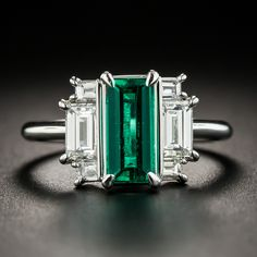 This geometrically designed, Art Deco influenced estate jewel features a gorgeous, elegantly elongated, crystalline green Colombian emerald weighing 1.04 carats. The vibrant gemstone glistens and glows between a sizable pair of bright-white baguette diamonds extended on the ends with a pair of smaller stones. 1.01 carat total diamond weight. A strikingly stunning, high-quality estate jewel hand fabricated in platinum. Currently ring size 6.