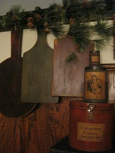 I love the old tins, the wooden cutting boards, and most of all the pine tree branches with pine cones.