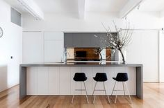 Going inverse on the previous waterfall counter edge designs, this looks to be a concrete countertop (with a glass cover) and white cabinets. It definitely brightens up the space, but I almost wish they'd foregone the glass cover. #ThisOldHouse inspiration via www.L-2-Design.com