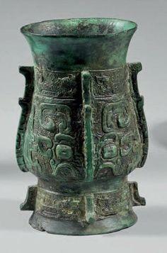 """Vase de forme """"hu"""" en bronze à patine verte à décor de masques de taotie et phénix sur fond de grecques, orné par des arêtes verticales. (Tr..."""