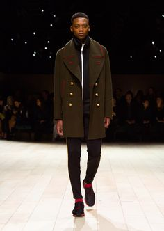 A dark green military pea coat layered over a black jersery tracksuit top and trousers and styled with lace-up weather Boot. Discover the collection at Burberry.com