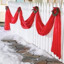 holiday home decor - Google Search  Red fabric draped in a swag-like-fashion & little green wreaths at the tops.