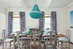 Pretty and chic. This decidedly simple white palette feels playful and glamorous paired with dramatic blue drapery and a modern, turquoise beaded chandelier. We are swooning over this eye catching and original dining room design.