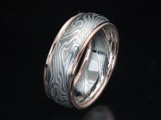 Unique wedding band shown in 8mm width of etched mokume of palladium 500 and sterling silver with 14K red gold round rails. Rails can also be in platinum, 18K yellow gold, 14K palladium white gold or palladium 950.
