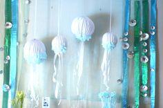 """Backdrop: paper lantern jellyfish, shiny ribbons, silver foil cupcake wrapper """"bubbles"""""""