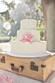 white wedding cake on a suitcase, because cakes like to travel too ... (; http://www.weddingchicks.com/2013/12/02/mccormick-home-ranch-wedding-3/