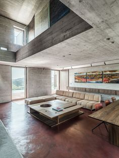 """Living Room, Coffee Tables, Sectional, Concrete Floor, Standard Layout Fireplace, Storage, and Recessed Lighting While the exterior """"faithfully interprets the typical formal themes of this Italian region,"""" says the architects, the inside is much more modern and minimalist. Reinforced concrete walls and ceilings meet a red concrete floor, which blends with the courtyard outside."""