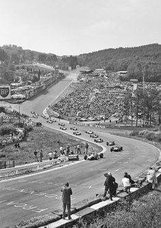 Formula 1 race cars approach the Eau Rouge corner at the Spa-Francorchamps circuit.