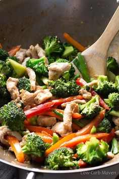 A bamboo spatula stirring a pork stir-fry of sliced pork, red bell peppers, orange bell peppers, scallions and broccoli in a carbon steel wok.