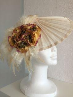 Tocado cono con flor y plumas. Base sinamay seda. sujeción con diadema. PVP: 40€