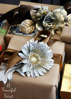 "Previous pinner said: ""I spray painted some dollar store silk flowers in matte gold and silver.  Then I tossed some large gold glitter sparkles on the petals while they were still wet.  Perfect parcel centerpieces me thinks?"""