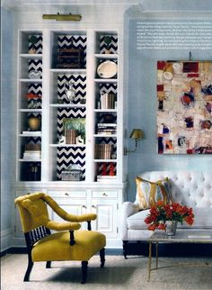 Graphic Patterns - chevron patterned wall paper behind a bookshelf adds a graphic touch to a traditional style room.