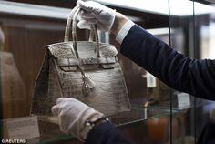 cba9c663eec An employee places an Hermes diamond and Himalayan Nilo Crocodile Birkin  handbag in a case.