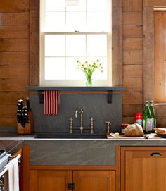 The soapstone countertop, with integrated sinks, forms one long, clean line. De Giulio treats his soapstone with Original Bee's Wax furniture polish.