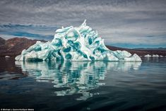 Nature at her most beautiful: This stunning iceberg was captured by American photographer Michael Quinn in the calm waters of Scoresby Sund,...