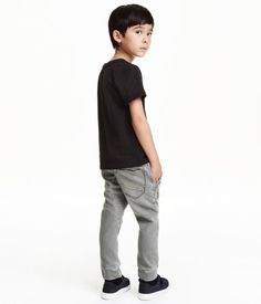 Gray. Jogger-style pants in soft stretch denim with an elasticized drawstring waistband. Side pockets, one back pocket, and tapered legs with ribbed hems.