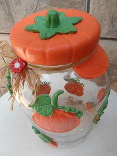 Pote de vidro com aplicação de abóboras em biscuit. <br>O modelo do vidro é de palmito com a boca estreita medindo 7,5 cm. A tampa é de plástico modelo de rosca.