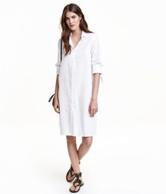 White. Short shirt dress in woven cotton fabric. Concealed fasteners at front, slits at sides, and long sleeves with cuffs and ties.