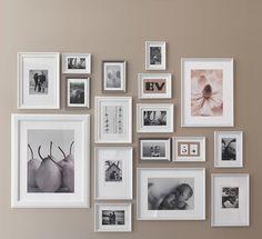 Eine graue Wand, u. a. dekoriert mit KNOPPÄNG Rahmen weiß lasiert in verschiedenen Größen. Darin zu sehen sind Familienfotos und Poster.