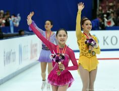 Women's singles winner Satoko Miyahara of Japan (C) waves to spectators with second placed Courtney Hicks of the US (R) and third placed Mao Asada of Japan (L) during the women's singles event at the ISU Grand Prix figure skating NHK Trophy in Nagano on November 28, 2015. AFP PHOTO / TOSHIFUMI KITAMURA (1329×1024)