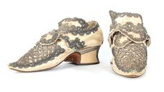 A fine pair of silver lace and ivory satin ladies shoes, circa 1720-30. with pointed toes which over-hang the white leather rand, low, wide heels, adorned overall with silver bobbin lace and silver strip passementerie, curved tongues, 26cm, 10in long