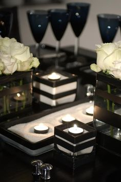 Scatter black votive candles in low containers amongst the flowers for a soft, warm glow.