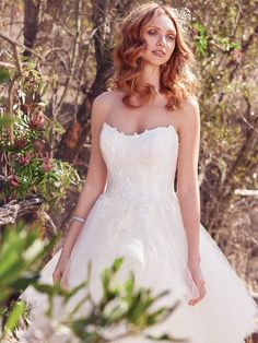 Maggie Sottero - KEISHA, This princess wedding dress features a ballgown skirt comprised of tiered layers of tulle trimmed in horsehair, with a romantic lace bodice and illusion back accented in lace. Finished with crystal buttons over zipper closure. Detachable illusion cold-shoulder cap-sleeves accented in lace appliqués sold separately.