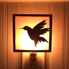 This handmade wooden nightlight measures roughly 5 x 5 inches and depicts the silhouette of a graceful hummingbird in flight. Vellum mounted behind the frame diffuses the light giving it a soft glow when lit.  This piece is mounted on a standard sized nightlight base and comes with one bulb.  Product Features: ------------------------  - Dimensions: 5 x 5 - Material: Poplar wood with vellum backing  - Surface: Pecan stain with lacquer finish - Other: Standard night light base and bulb…