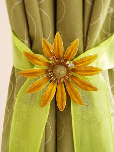 A vintage pin adorns a ribbon for a pretty curtain tieback. Wrap sheer ribbon around the curtain panel and tie, leaving tails about a foot long. Pin the flower brooch at the knot. Brooches like this one are easy to find.