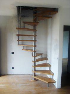 Scala a chiocciola a base quadrata, gradini in massello di faggio, barriera in acciaio inox satinato.