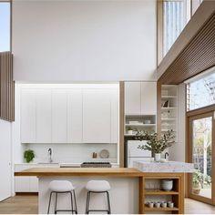 O branco usado na marcenaria acentuou a atmosfera cheia de luz desta cozinha! O espaço ainda recebeu toques de cor e calor com a madeira dos caixilhos e bancada! Projeto de Poco Archi e foto de Tatjana Plitt.