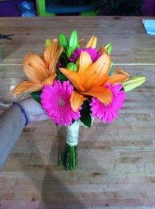 Ramo de novia primaveral compuesto por liliumns naranjas y gerberas fucsias