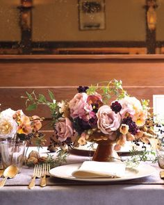 """For the impressionistic centerpiece below, Gill showcased his newest botanical obsession, 'Koko Loko' roses, whose colors change from mocha brown to mauve as they bloom. Peach and plum pansies, chocolate cosmos, bell-shape flowering maple, inky privet berries, and clematis vine round out the scene. Gilded walnuts also make an appearance, tucked into the arrangements and scattered along the table. """"For a twist, you could fill the compotes entirely with nuts instead of flowers,"""" says Gill…"""