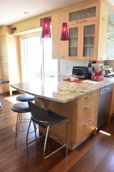 cuisine en bois merisier naturel, comptoir en granite luminaire rouge,