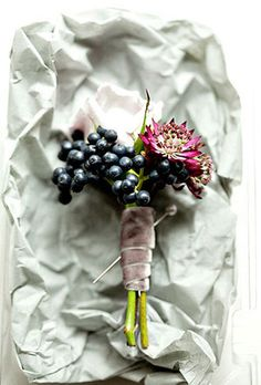 Wedding boutonniere of scabiosa, viburnum berries, and astrantia by Sullivan Owen Floral & Event Design Browse more wedding boutonnieres.