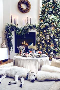 great room setup: evergreen garland on mantel + tall, dark tapers on mantel + large wreath over mantel + cray-zay full tree next to