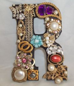 wooden letters that are painted black and then covered with vintage, repurposed jewelry: