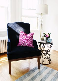 White walls, white lamp, navy velvet-upholstered chair with dark wooden legs and a bright pink patterned pillow, light wood floors, blue and white patterned rug, black sculptural side table, and flowers in a glass vase