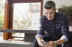 Business man text messaging in office lobby Stock Photo