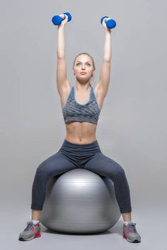 beautiful blonde girl in sportswear does exercises with dumbbells on