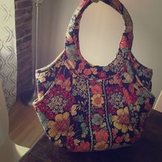 Vera Bradley Tote/ handbag Beautiful colors! Coral, Aqua, Red, Yellow against a black backdrop. Roomy with exterior side pockets too! Handles ever so slightly faded where it hangs on your shoulder. Not noticeable Vera Bradley Bags Totes