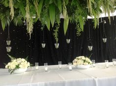 Tropical rain forest?  YES IT IS!!!  This wedding was amazing.  Three 20' hanging panels with various greenery, LED votive candles with a black LED twinkle light curtain back drop. STUNNING!  DAVE