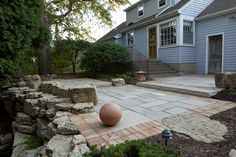 Terraced limestone patio with brick border.  Boulders scribed into the patio provide additional seating and visual interest.