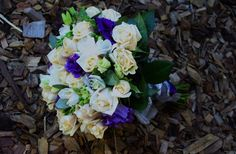 Posy style bouquet of champagne roses, white freesias and purple lisianthus. Accented with purple and white ribbon wraps.