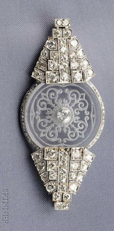 Art Deco Platinum, Diamond, and Rock Crystal Brooch, centering a scroll-etched rock crystal disk flanked by box-set full-cut diamonds, rose-cut diamond accents, approx. total wt. 2.50 cts., millegrain accents, lg. 2 3/8 in.