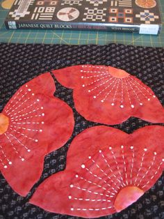 """Another block from """"Japanese Quilt Blocks to Mix & Match"""" by Susan Briscoe.  I used freezer paper templates for the flower shapes and pearle cotton for the embroidery.  The flower centers shapes were very difficult to get uniform and smooth.  Block measures 9""""."""