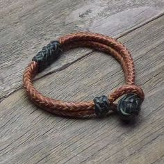 A Herringbone braid without a core, sometimes also called a square braid, in Whiskey leather kangaroo leather with Black knots. Being it is braided without a core this bracelet is 3/16 of an inch in diameter. While it retains a bit of a square shape the process of rolling the braid out gives it a rounded edge. A length of 8 strand braid is double to make this style of bracelet. The braid is done in 3/32 inch wide strands and is roughly a 3/8 inch wide at the center where the do...