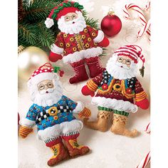 <li>Create this wonderful set of Santas to decorate your holiday tree or give as a gift<li>Kit featuring Mary Engelbreit design includes: felt, sequins, floss, needle and step-by-step instructions<li>Each Santa measures 5 inches wide x 6.25 inches high