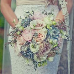 Peonies, roses and succulents in a handtie style. Looks pretty with her lace dress behind.